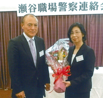 職警連総会で高橋会長から花束を受け取る磯部さん(右)