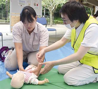 乳児に心臓マッサージを行う参加者