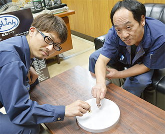 回し手の岩佐さん(右)と同じ生産部の樋口博亮さん
