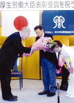 新倉会長から花束を受け取る相澤夫妻