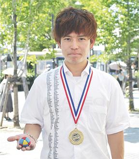 メダルを首に、バッグを手に持つ石田さん
