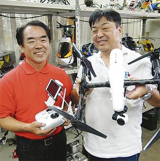 大会で使ったドローンの実機を持つ依田さん(右)とリモコンを持つ吉田さん