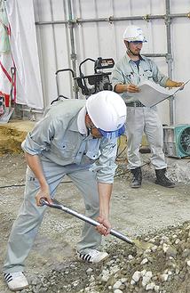 砕石敷込み作業を手伝う益子副校長(手前)