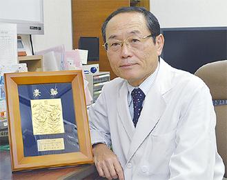 受賞の楯を見せる田村さん