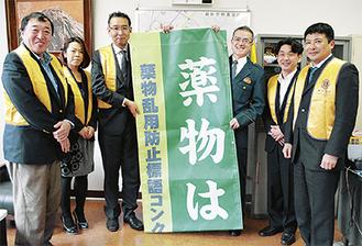 垂れ幕を掲げる飯島署長(右から3番目)とLC会員ら