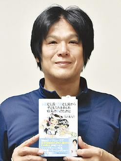 著書を手に笑顔を見せる江口さん