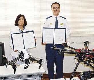 協定書を持つ依田社長(左)と飯島署長