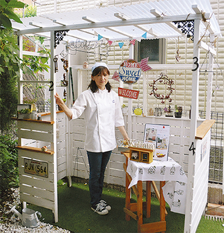 庭に設置した自作の「女子小屋」に立つ高崎さん