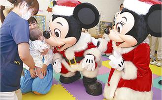 赤ちゃんと触れ合うミッキーとミニー