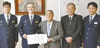 飯島署長に目録を手渡す川口会長(中央)