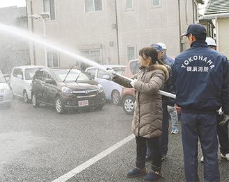 自動車に向けて放水する参加者