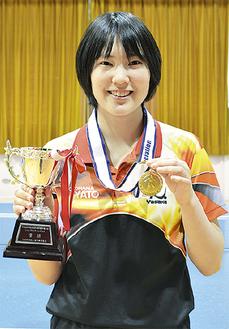 優勝トロフィーとメダルを掲げ、笑顔の笹尾さん