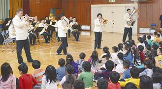 音楽隊の演奏を楽しむ児童ら