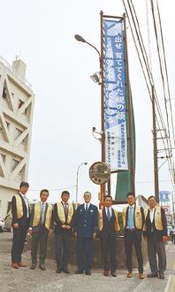 設置した垂れ幕の前に並ぶ飯島署長(中央)とLC会員ら