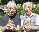 作った蜂蜜を持つ奈良部理事長(右)と高野登さん