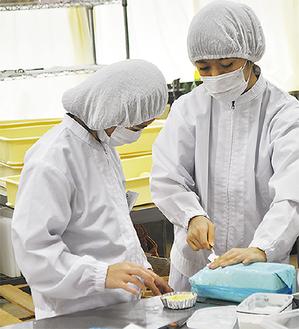 教員(右)の指導を受けながら、パン作りに挑戦する生徒