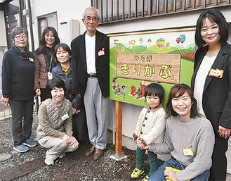 小林代表(写真中央)とスタッフら。看板は、小林代表の友人たちが手作りした