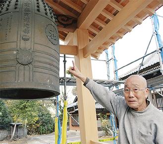 鐘に刻まれた「和」の字を説明する栁澤住職