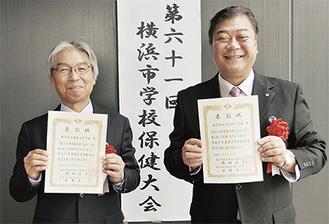 表彰状を手に喜ぶ鈴木校長(右)と山川校長