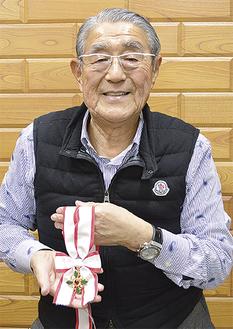 笑顔で金章を持つ川口会長
