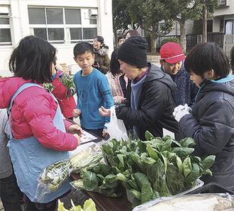 小松菜を販売する児童たち(同校提供)