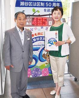 区役所2階に設置されたカウントダウンボードの前で選出を喜ぶ廣木さん(右)と、網代委員長