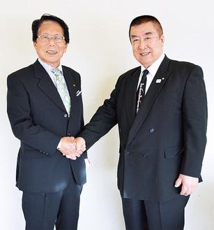 握手を交わす石垣前会長(左)と伊藤会長