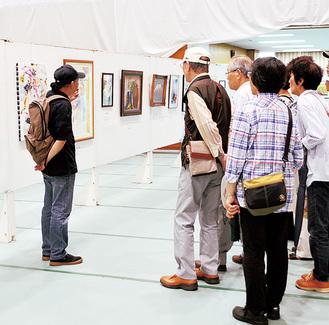 作品を解説する浅野さん(左)