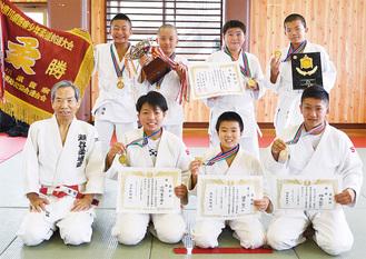 須藤会長(前列左)と、笑顔を見せる優勝メンバー