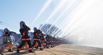 空に向かって放水する消防団員