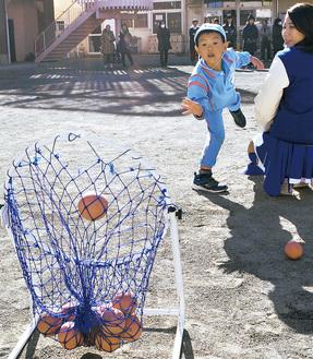 全身でボールを投げる園児