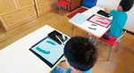特殊な半紙を使い、文字を書く子どもたち
