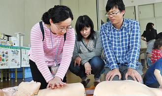 参加者に心臓マッサージを教えるキさん(左)