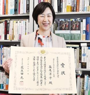 表彰状を手にする長尾さん(3月19日、研究室で)
