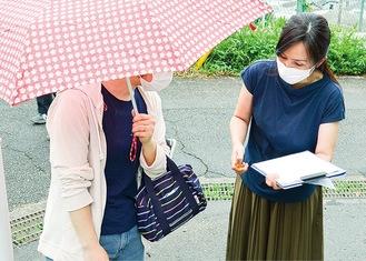 雨のなか、署名を集める保護者
