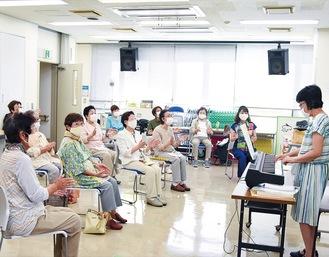 原田さん(右)が弾くメロディーに合わせて、手拍子とハミングで楽しむ参加者