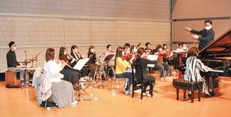 指揮者の奥村さんのもと、本番に向けて練習に励む出演者ら=11月3日