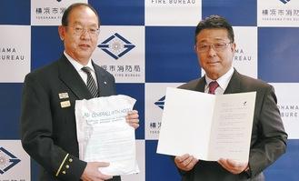 防護服を手に持つ松原局長(左)と飯島社長