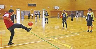 コーチに見守られながらペアを組んでボールを蹴った