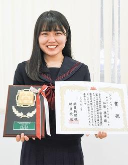 賞状と作品が刻まれた盾を持つ加藤さん