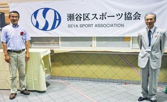 ロゴマークが描かれた横断幕と考案者の大貫さん(左)、澁谷会長