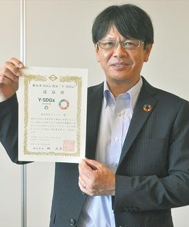 認証状を持つ相澤副社長。SDGsのバッジをスーツに付けて普及を図る