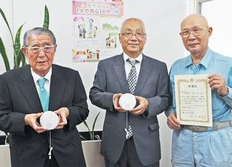住警器を持つ川口会長(左)と早坂代表(中央)。石川会長が手にするのは、エイシンに贈られた感謝状