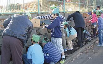 地域ボランティアと植栽する児童