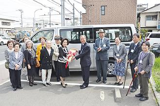 寄贈した車の前でキーのレプリカを渡す内藤会長(左)と新村理事長(右)