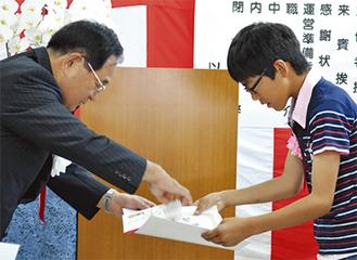 相澤社長から感謝状を受け取る山野井君(右)