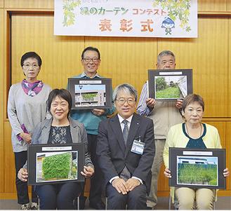 下村区長(前列中央)と作品の写真を手にする受賞者ら