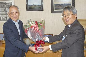 下村区長から祝いの花束を受け取る石田さん(左)