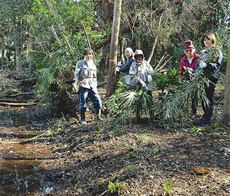 湧水が流れる小川のそばで作業中の会員ら