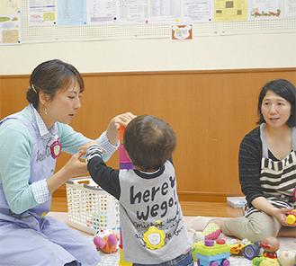 子どもと遊ぶ井田さん(左)と菅野さん(右)